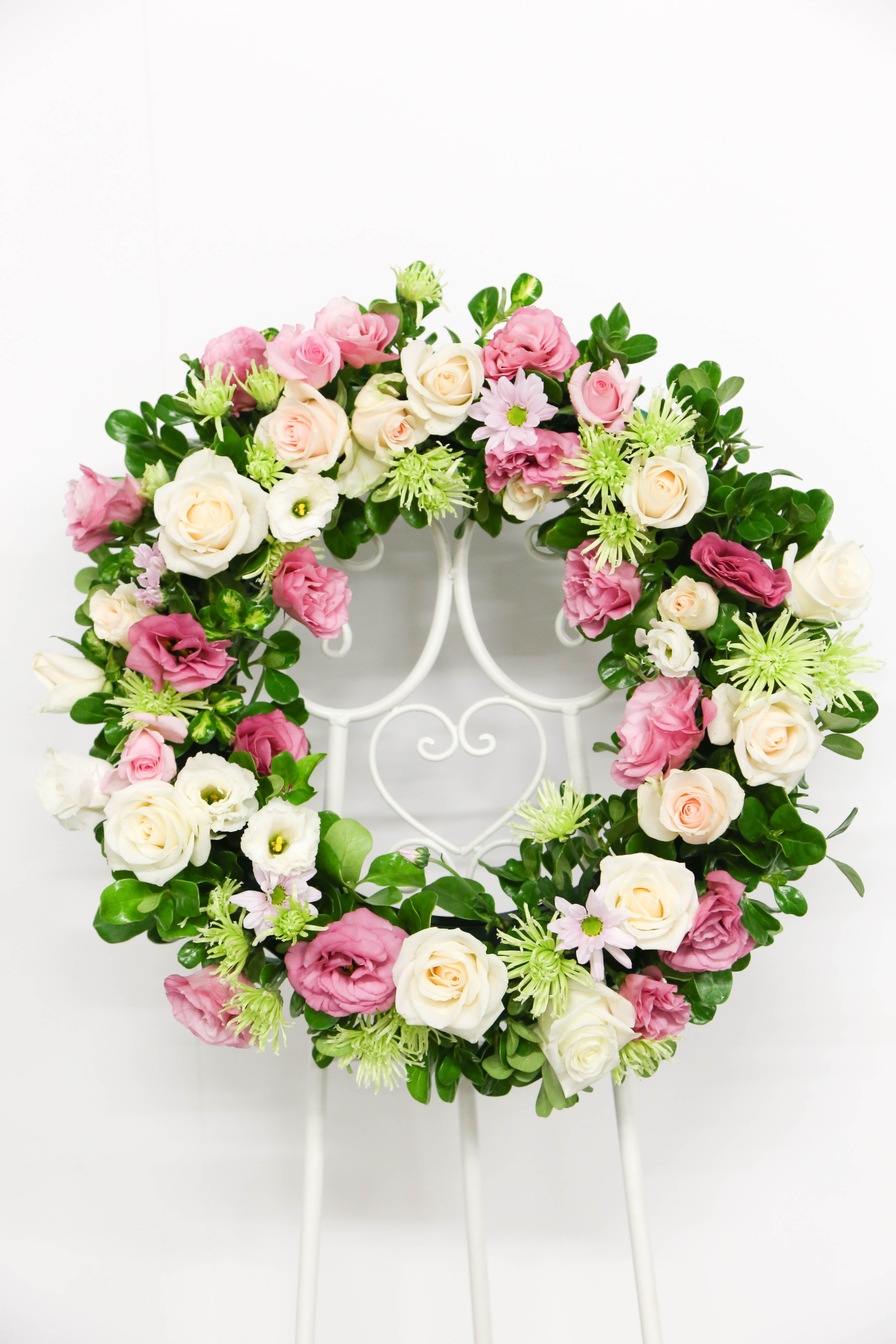 Wreath of pastel blooms including roses